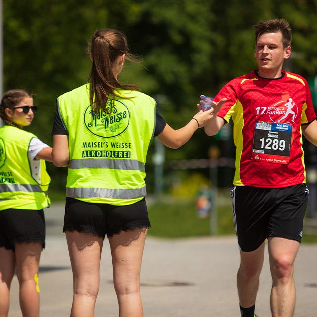 Volunteer reichen einem Läufer Wasser